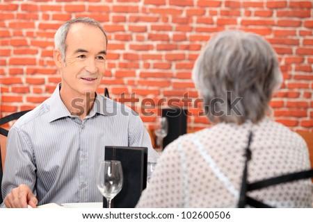 Elderly couple having meal in restaurant - stock photo