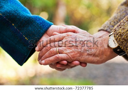 Elderly couple holding hands outdoors. - stock photo