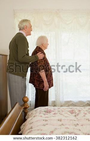Elderly couple in bedroom - stock photo