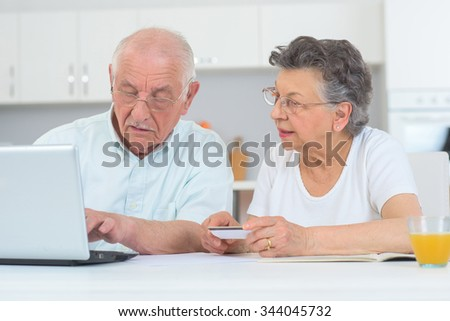 elderly couple in front of the laptop at home