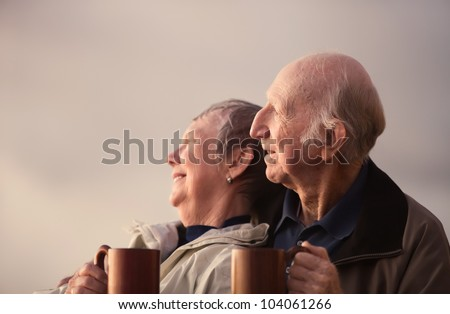 Elderly couple in jackets looking away to the light - stock photo