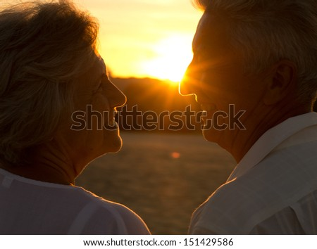 Elderly couple in love at sunset on a summer evening - stock photo