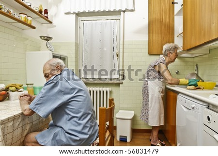 elderly couple in the kitchen - stock photo