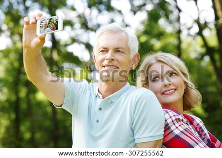 Elderly couple making a self portrait while taking an excursion in the forest - stock photo