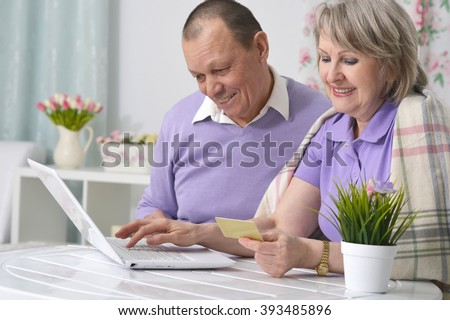 elderly couple making purchases over the Internet by credit card - stock photo