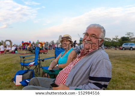 Elderly couple of spectators sitting in deckchairs at an outdoors event on a field turning to smile at the camera - stock photo