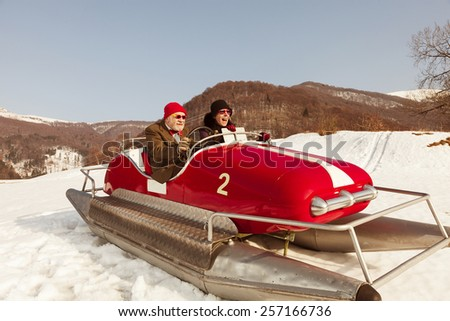 Elderly couple on a pedalo in the snow - stock photo