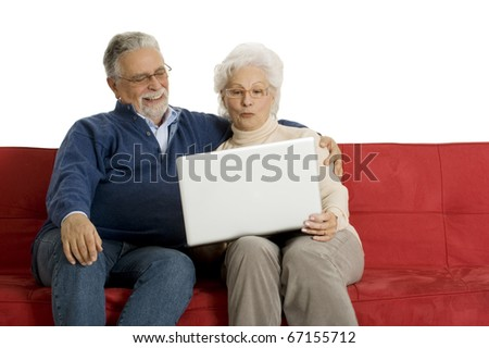 elderly couple on the sofa using a laptop - stock photo
