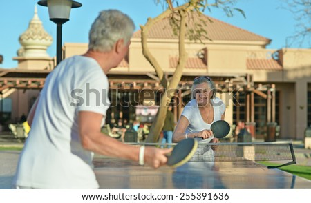 Elderly couple playing ping pong at hotel yard - stock photo