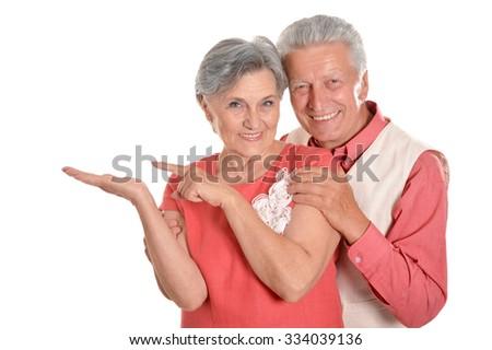 Elderly couple pointing on a white background - stock photo