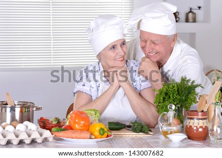 elderly couple preparing vegetable salad together - stock photo
