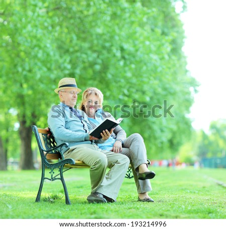 Elderly couple reading a book seated on a bench in park shot with tilt and shift lens  - stock photo