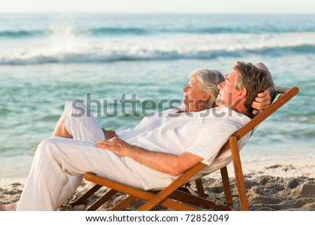 Elderly couple relaxing in their deck chairs - stock photo