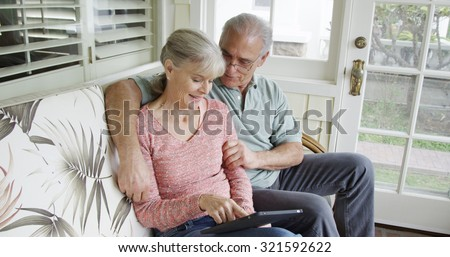 Elderly couple relaxing using tablet on couch at home - stock photo