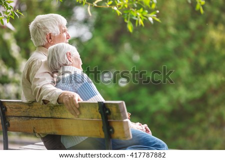 Elderly couple resting on a bench in the park - stock photo