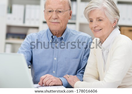 Elderly couple sharing a laptop computer as they read information on the screen while sitting in an office - stock photo