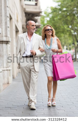 Elderly couple shoping in the city - stock photo