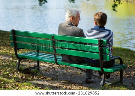 Elderly couple sitting on a bench in park - stock photo