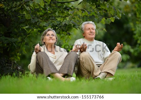 Elderly couple sitting on the grass in lotus pose