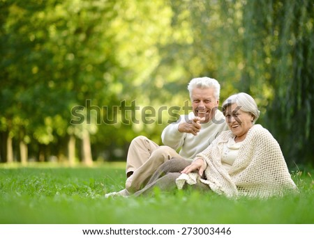 Elderly couple sitting together at autumn park grass - stock photo