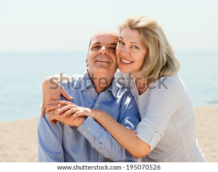 elderly couple spends time on seaside - stock photo