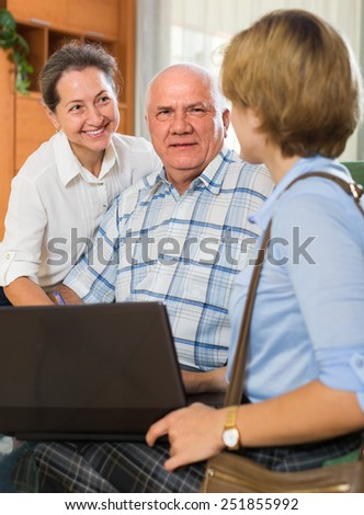 Elderly couple talking with social worker with laptop at home and smiling. Focus on man