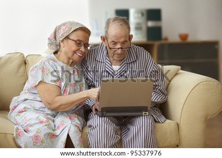 Elderly couple using a laptop - stock photo