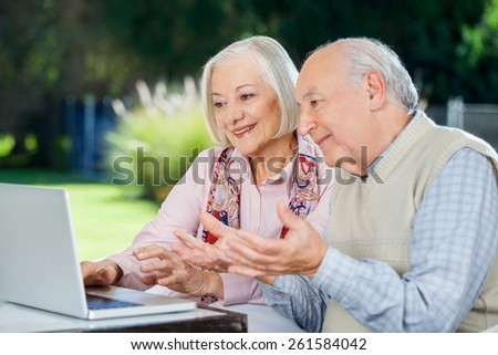 Elderly couple video chatting on laptop while sitting at nursing home porch - stock photo