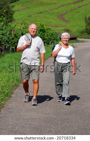 elderly couple walking in through vineyards