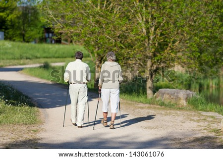 Elderly couple wandering with nordic walking sticks inside the park together. - stock photo