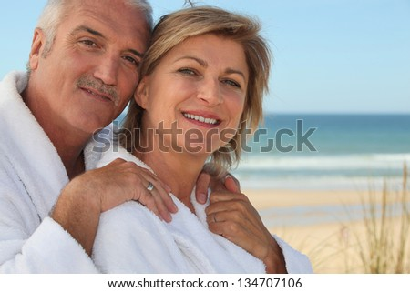 Elderly couple wearing white at the beach - stock photo