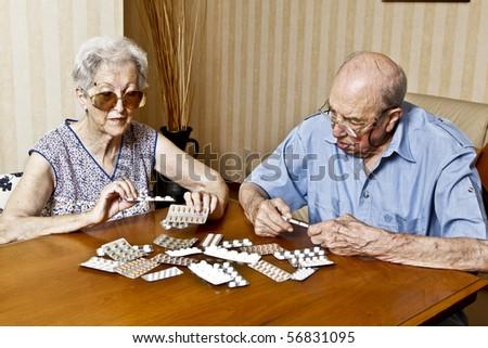 elderly couple with pills - stock photo