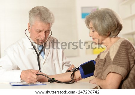 Elderly doctor measuring blood pressure of the senior woman - stock photo