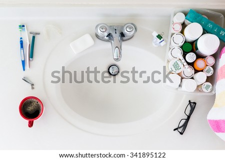 Elderly domestic bathroom sink with medicines and coffee in the morning - stock photo
