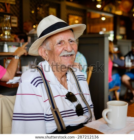 Elderly eighty plus year old man wearing a hat in a restaurant setting. - stock photo
