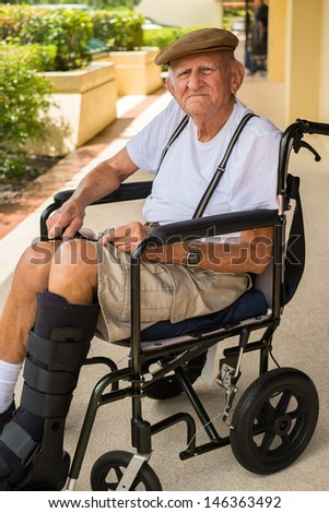 Elderly eighty plus year old man with a fractured leg in a wheel chair outdoors.