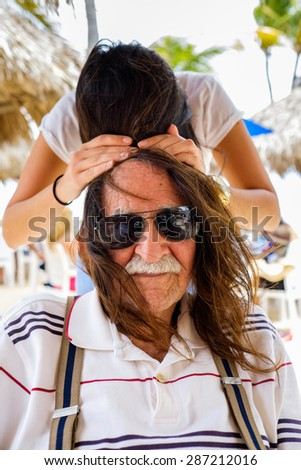 Elderly eighty plus year old man with granddaughter outdoors having fun. - stock photo