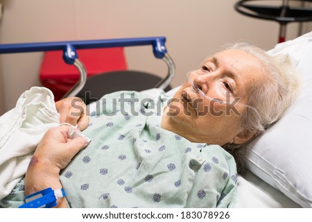 Elderly eighty-plus-year-old woman in a hospital bed. - stock photo