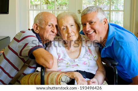 Elderly eighty plus year old woman in a wheel chair in a home setting with her husband and son. - stock photo