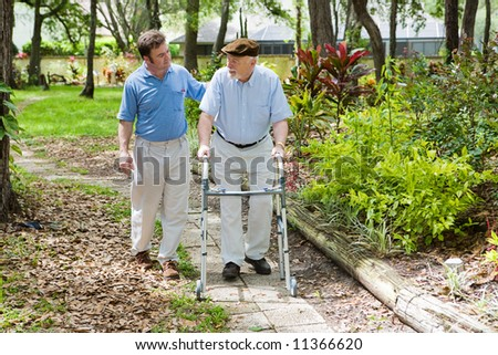 Elderly father and adult son out for a walk in the park. - stock photo