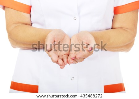 Elderly female doctor or nurse presenting something on open palms - stock photo