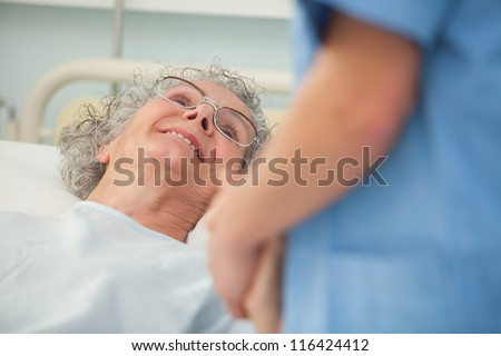 Elderly female patient looking up at nurse from hospital bed - stock photo