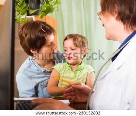 Elderly female pediatrician doctor examining preschooler at clinic office - stock photo