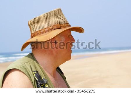 Elderly fisherman on beach - stock photo
