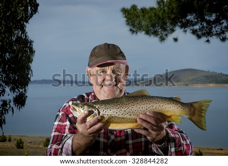 Elderly fisherman proudly shows off his brown trout - stock photo