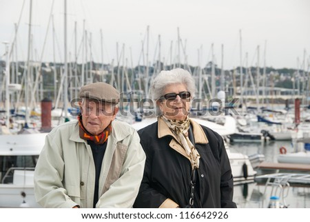 elderly french couple walking together at the yacht harbor of brest in brittany - stock photo