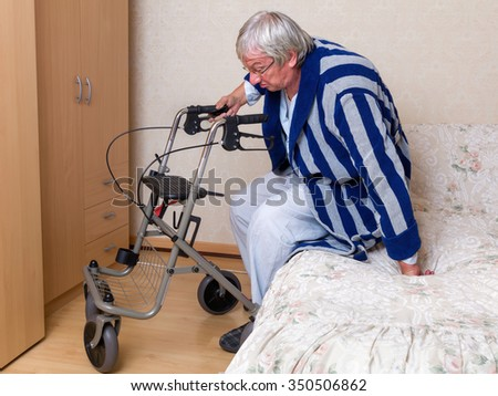 Elderly grandfather in nursing home using a rollator in his pajama - stock photo