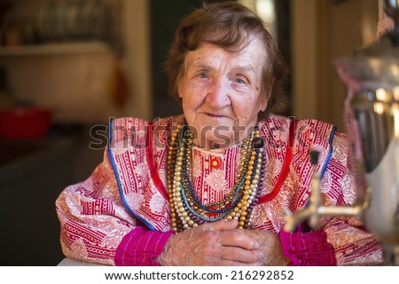 Elderly grandmother in ethnic clothes sitting in his house. - stock photo