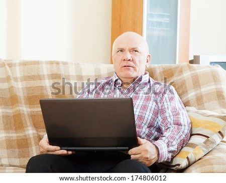 elderly gray-haired man working at his laptop on  sofa at home - stock photo