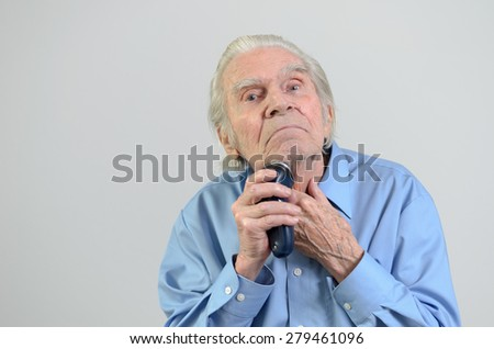 Elderly groomed man wearing a tidy blue shirt while shaving himself with a cordless battery-powered electric razor or shaver, portrait with copy space on gray